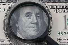 Money expertise. Magnifying glass and fragment of one hundred dollar bill with portrait of president Benjamin Franklin Stock Photography