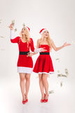 Money fallen around excited sisters twins standing and smiling Stock Image