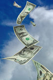 Money falling in clouds. Dollar bills falling from the sky with clouds Stock Photo