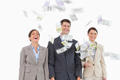 Money falling down on smiling businessteam Royalty Free Stock Photos