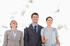 Money falling down on smiling salesteam Stock Photo