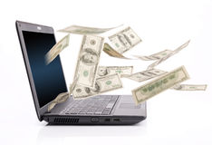 Money falling from laptop screen Royalty Free Stock Photo