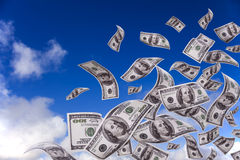 Money falling from the sky. Lots of dollar bills falling from the sky royalty free stock image