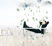 Money falling from the sky on businessman resting on a chair at. City background concept, close up royalty free stock images