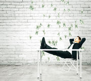 Money falling from the sky on businessman resting on a chair in Stock Photo