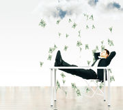 Money falling from the sky concept with businessman sitting on a Royalty Free Stock Photography