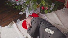 Money falls on a man sleeping near a Christmas tree. Falling dollars. A man is sleeping near a Christmas tree hd stock footage