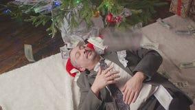 Money falls on a man sleeping near a Christmas tree. Falling dollars. A man is sleeping near a Christmas tree hd stock video footage