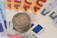 Money fan with coins. Bank notes widespread with 2 Euro coins on top Stock Photography