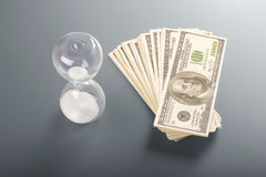 Money fan beside hourglass. Stock Images