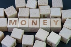 Money, finance or savings concept by cube wooden block with alphabet building the word Money at the center on dark blackboard stock images