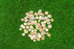 Money and Finance Topic: cash coins lie on the green grass top view Royalty Free Stock Photo