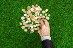 Money and Finance Topic: Money coins and human hand in black suit showing gesture on a background of green grass top view Royalty Free Stock Images