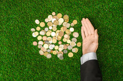 Money and Finance Topic: Money coins and human hand in black suit showing gesture on a background of green grass top view Stock Image