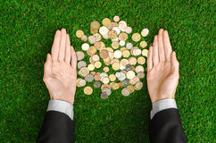 Money and Finance Topic: Money coins and human hand in black suit showing gesture on a background of green grass top view Royalty Free Stock Photos