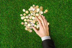 Money and Finance Topic: Money coins and human hand in black suit showing gesture on a background of green grass top view Stock Photos