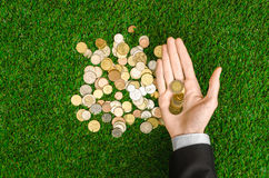 Money and Finance Topic: Money coins and human hand in black suit showing gesture on a background of green grass top view Stock Photography