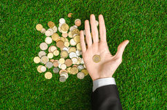 Money and Finance Topic: Money coins and human hand in black suit showing gesture on a background of green grass top view Royalty Free Stock Photography