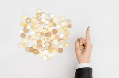 Money and Finance Topic: Money coins and human hand in black suit showing gesture on a gray background top view royalty free stock photo