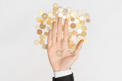 Money and Finance Topic: Money coins and human hand in black suit showing gesture on a gray background top view Stock Images