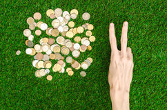 Money and Finance Topic: Money coins and human hand showing gesture on a background of green grass top view Stock Photo