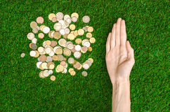 Money and Finance Topic: Money coins and human hand showing gesture on a background of green grass top view Royalty Free Stock Photos