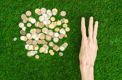 Money and Finance Topic: Money coins and human hand showing gesture on a background of green grass top view Royalty Free Stock Photo
