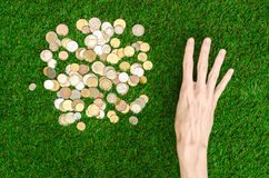 Money and Finance Topic: Money coins and human hand showing gesture on a background of green grass top view Stock Photos