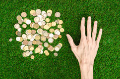 Money and Finance Topic: Money coins and human hand showing gesture on a background of green grass top view Royalty Free Stock Image