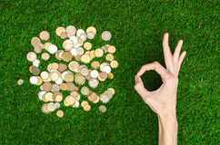 Money and Finance Topic: Money coins and human hand showing gesture on a background of green grass top view Royalty Free Stock Images