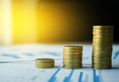Money and financial concept, stack of coin on many business docu. Ment graph with sunlight in the morning Royalty Free Stock Image