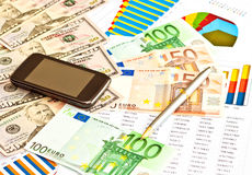 Money, financial graphs, phone Stock Photography