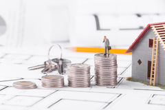 Businessman standing on coins next to the cottage. The concept of earning and spending money stock image