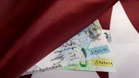 Money on Flag Of Qatar. Banknotes on Flag Of Qatar dolly shot stock footage
