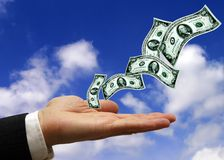 Money is flying. Hand of a businessman open with dollars banknotes flying from it stock images