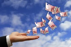 Money is flying. Hand of a businessman open in front of a blue sky with euro banknotes flying royalty free stock photo