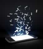 Money flying out of a touchscreen phone Stock Photo