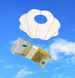 Money flying on a parachute isolated on white Stock Images