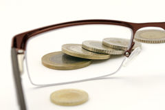 Coins seen through eyeglasses Royalty Free Stock Photos