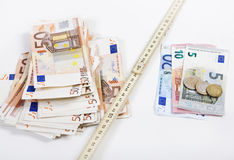 Money folding rule. The folding rule between poverty and wealth goes further apart, illustrated with euros Royalty Free Stock Photo