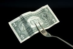 Money for food. A bank note in a metal fork Royalty Free Stock Images