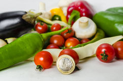 Money and food. Concept-one euro coin and vegetables on white background Stock Photo