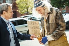 White collar worker giving money for food to homeless. Money for food. Successful supportive white collar worker giving money for food to homeless men standing royalty free stock images