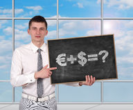 Money formula. Businessman standing in office and holding blackboaard  with money formula Royalty Free Stock Photography