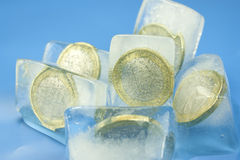 Money frozen. 1 euro coins into ice cubes Stock Photo