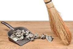 Money in the garbage scoop. Broom sweep crumpled dollars in a dustbin on wooden table, isolated on a white background Royalty Free Stock Image