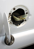 Money in Gas Tank. Money down the gas tank Stock Photo