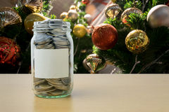 Money in the glass bottle with decorated Christmas tree backgrou Royalty Free Stock Photos