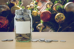Money in the glass bottle with decorated Christmas tree backgrou Stock Photos