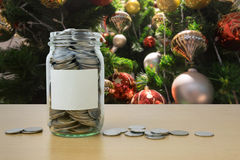 Money in the glass bottle with decorated Christmas tree backgrou Stock Photo